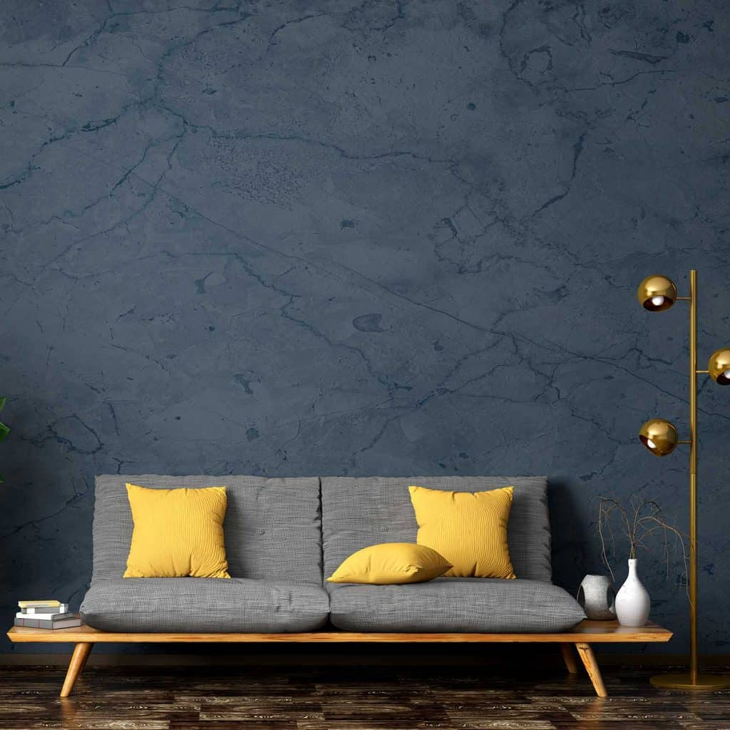 Modern interior of living room with gray sofa, yellow throw pillows and floor lamp against blue stucco wall