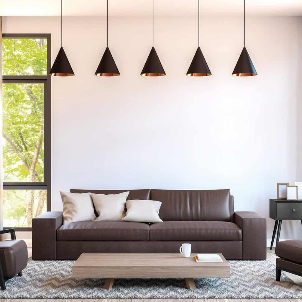 Modern living room decorate with brown leather furniture, wooden coffee table, carpet and throw pillows