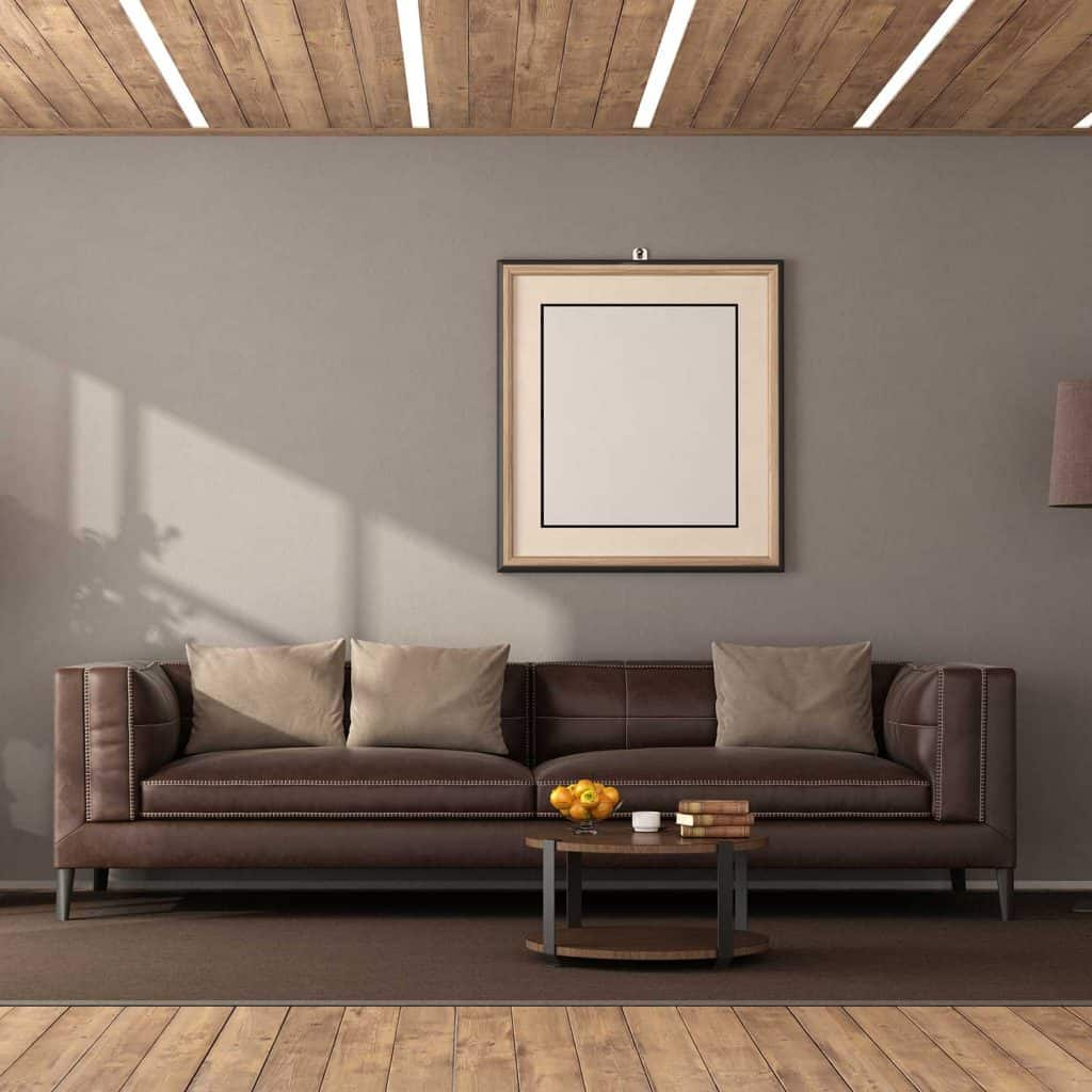 Modern living room with brown leather sofa and led light on wooden ceiling