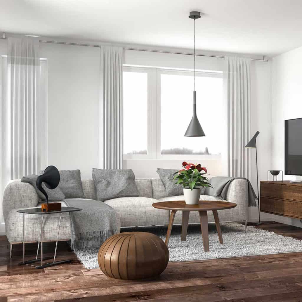Modern living room with gray corner sofa, coffee table, tv and hardwood floor