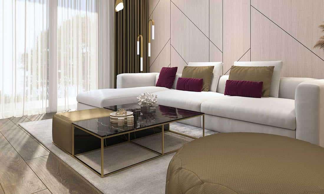 Modern living room with white corner sofa and light gray carpet on wooden floor