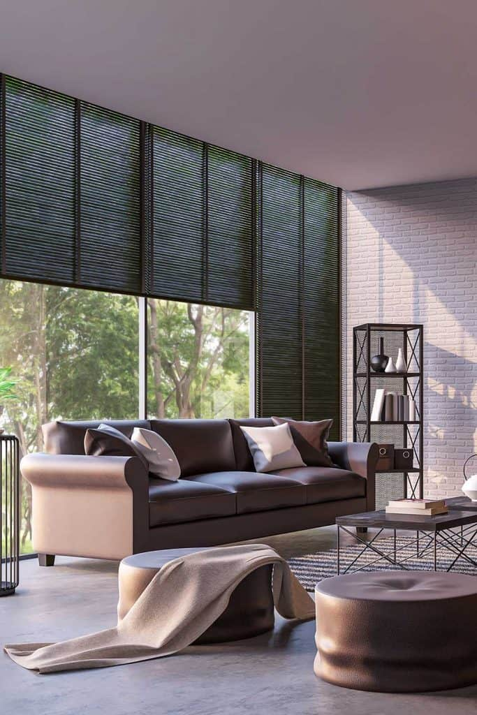 Modern loft living room with nature view, brown leather sofa and white brick walls