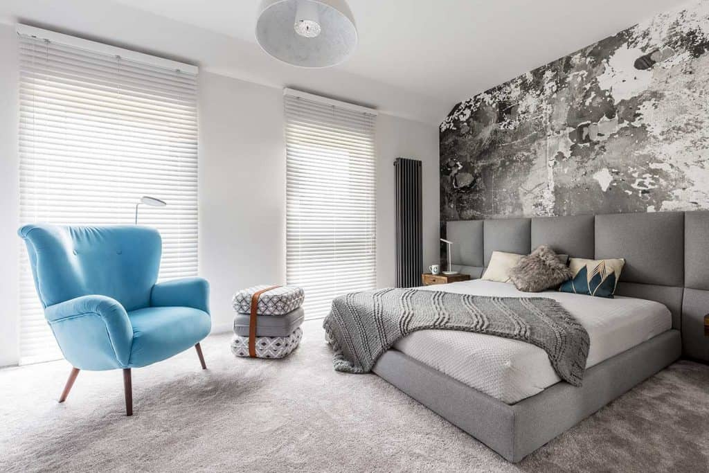 Monochromatic gray bedroom with grunge wall, wooden bedside table, white walls and blue vintage style armchair