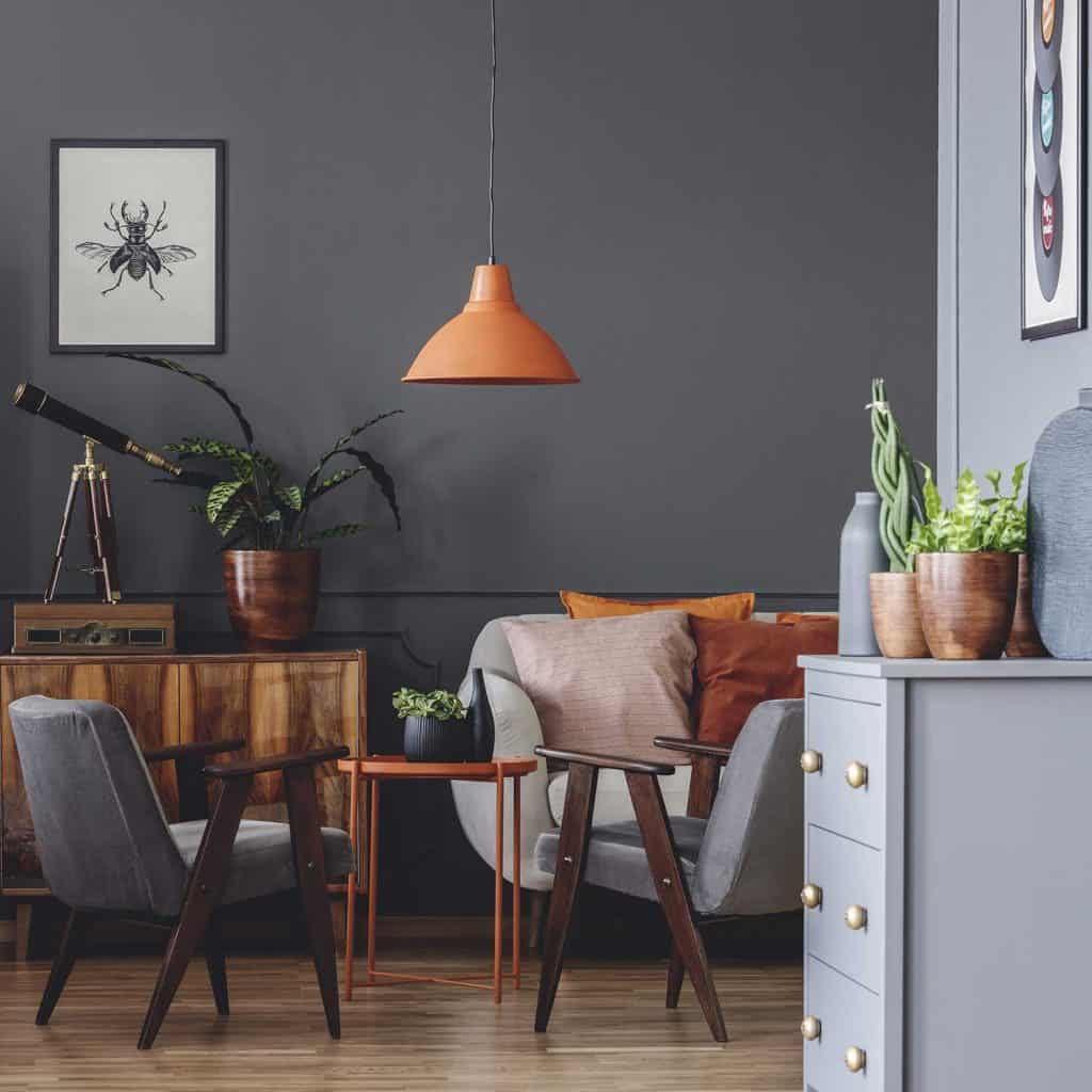 Orange lamp above table and gray armchair in dark vintage living room interior with posters