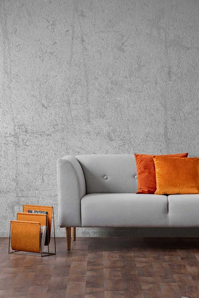 Orange pillows on gray settee in living room interior with concrete wall and wooden floor