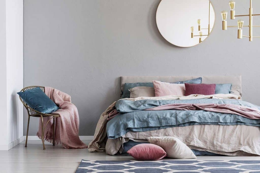 Pastel pink, beige and blue bedding on king size bed in trendy bedroom interior