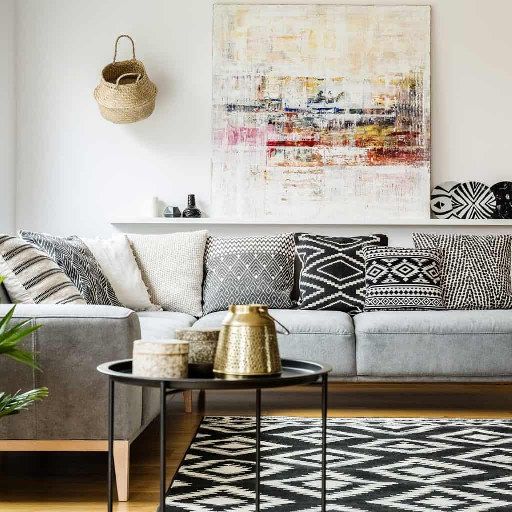 Patterned pillows on grey corner sofa in living room interior with coffee table and abstract painting decor