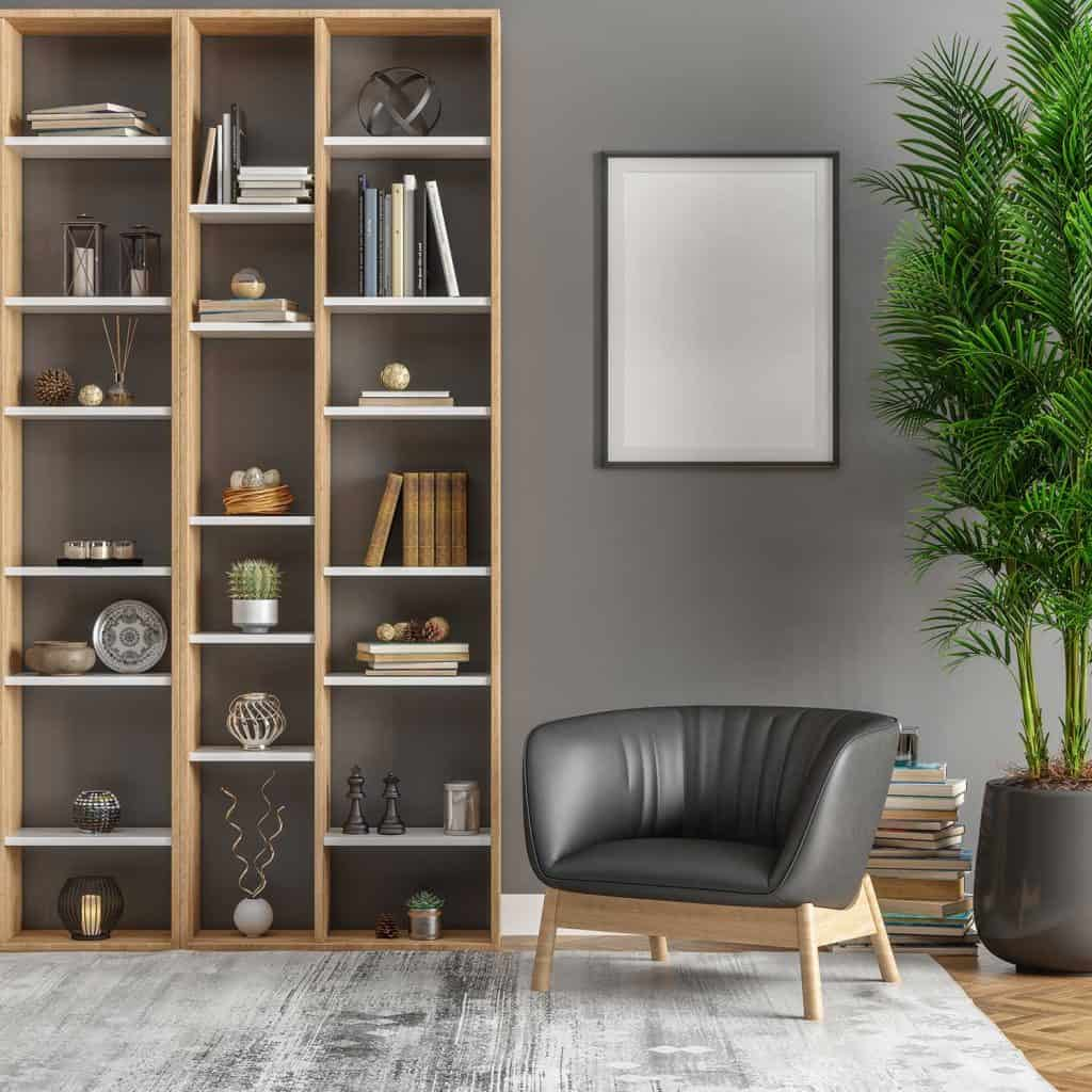 Picture frame above gray accent chair, bookshelf and plants in living room interior