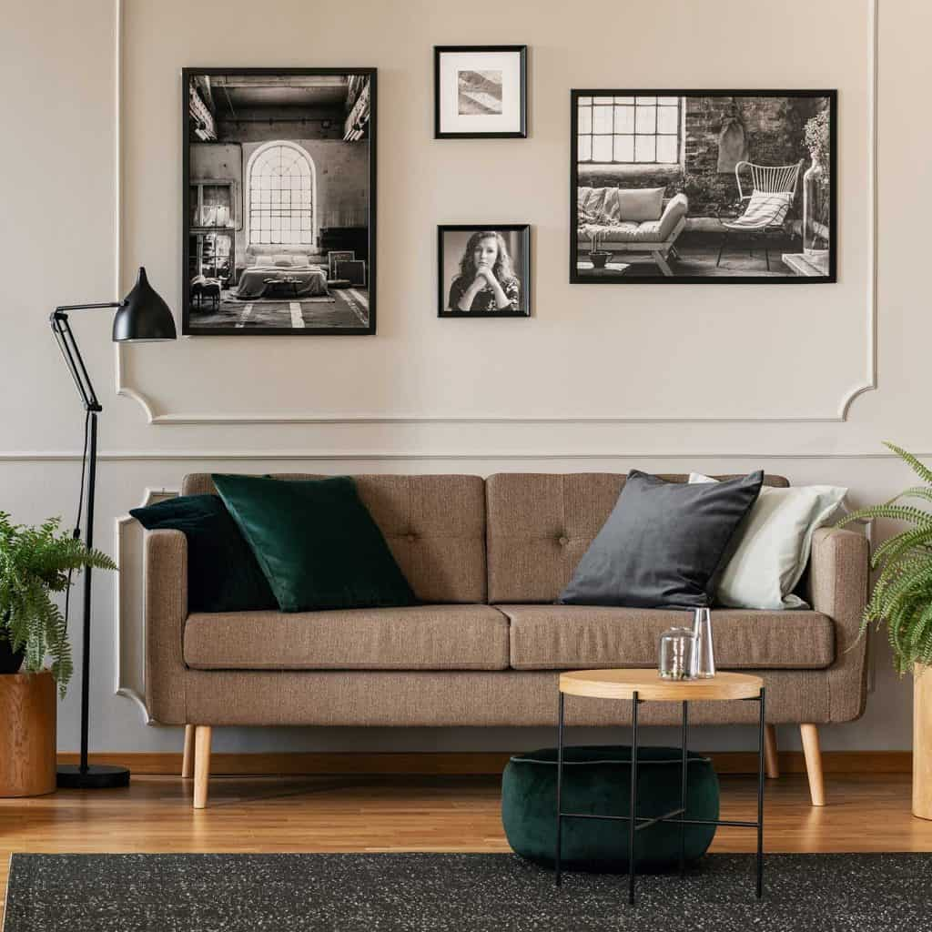 Pillows on brown sofa in fashionable living room with framed pictures on wall
