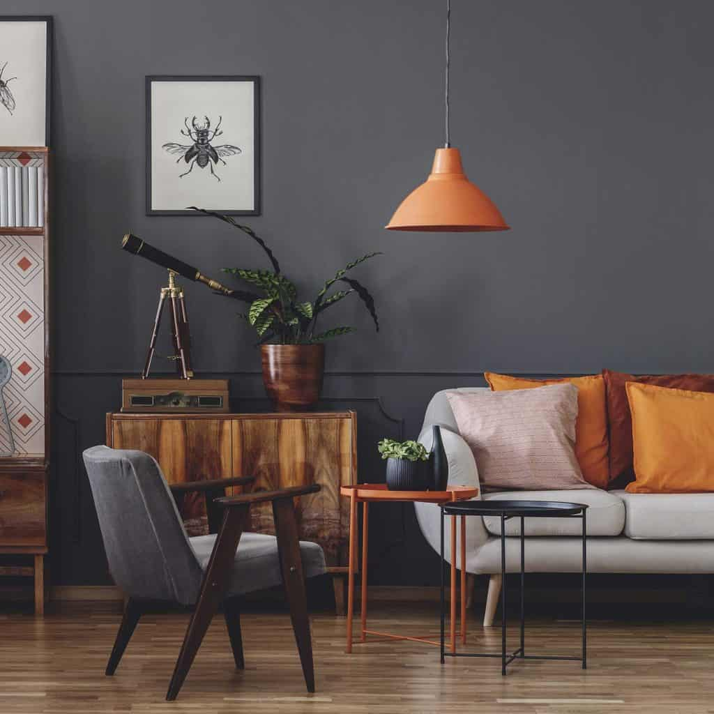 Posters on gray wall in vintage living room interior with wooden armchair next to orange table with plant