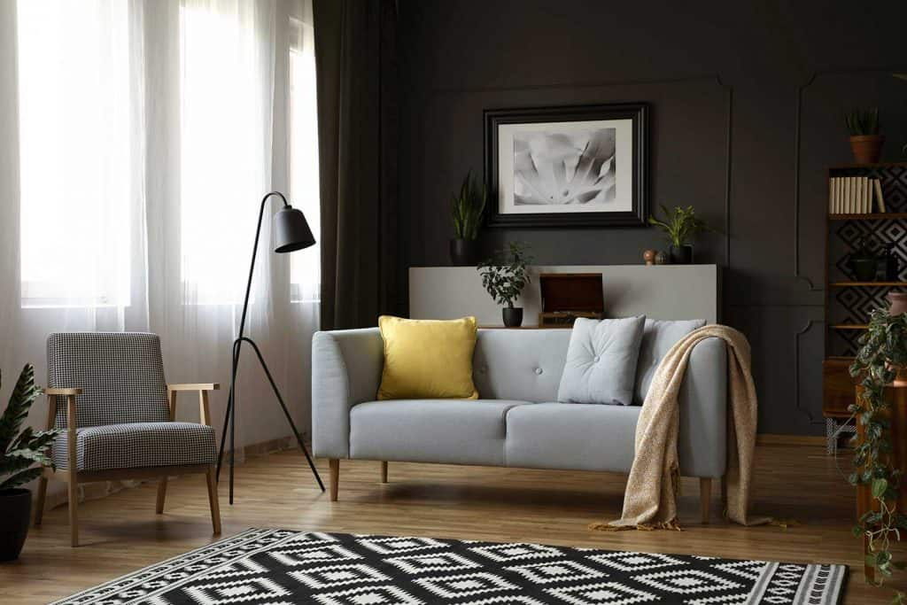 Retro armchair, sofa decorated with pillows and modern lamp, painting and carpet in a living room interior