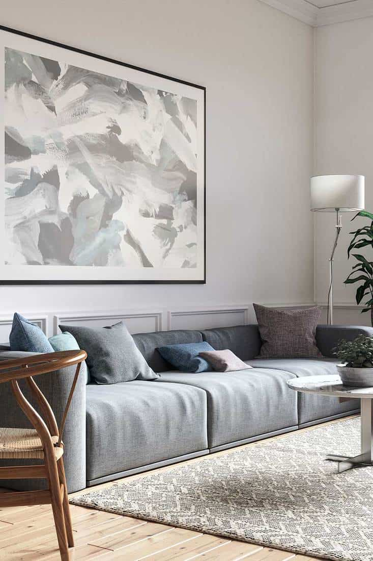 Scandinavian interior design living room with grey sofa, round coffee table and abstract wall art decor
