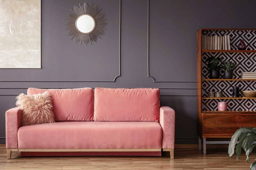 Simple, pink sofa with a fur pillow next to a wooden cupboard in living room interior with gray wall and mirror