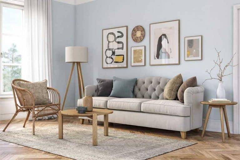 Small light blue colored wall living room with gray couch with pictures above it, 32 Beige Couch Living Room Ideas [Inc. Pictures!]