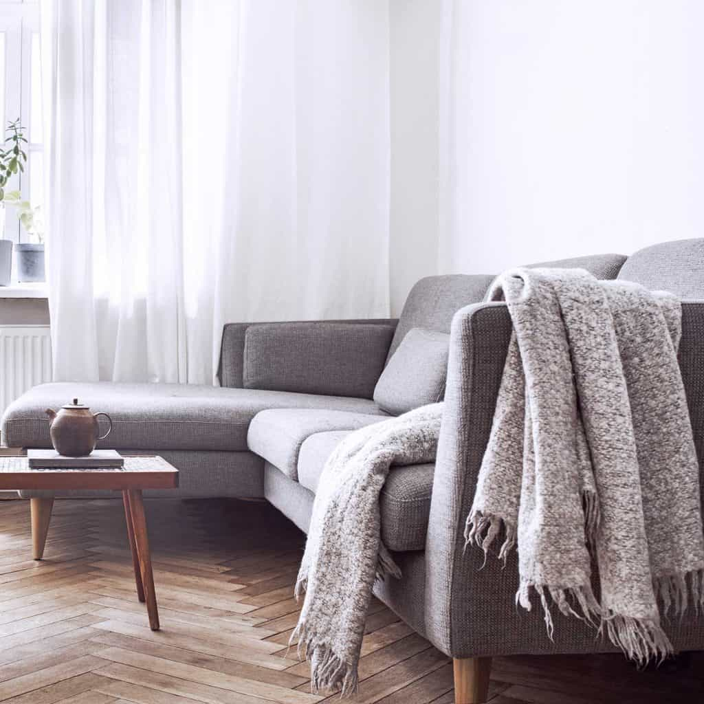 Stylish scandinavian interior living room with small design table and grey sofa with blanket