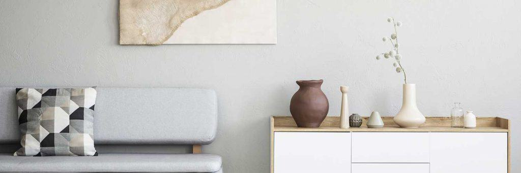 Throw pillow on a gray sofa and a white wooden cabinet