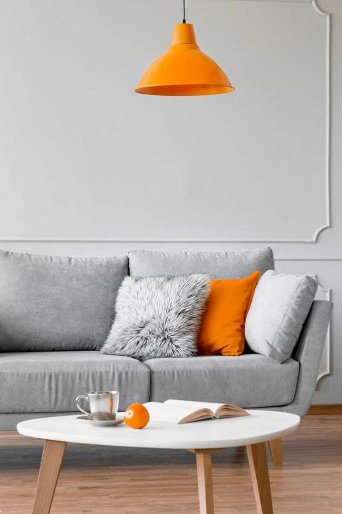 Throw pillows on a gray couch and coffee table in a living room interior
