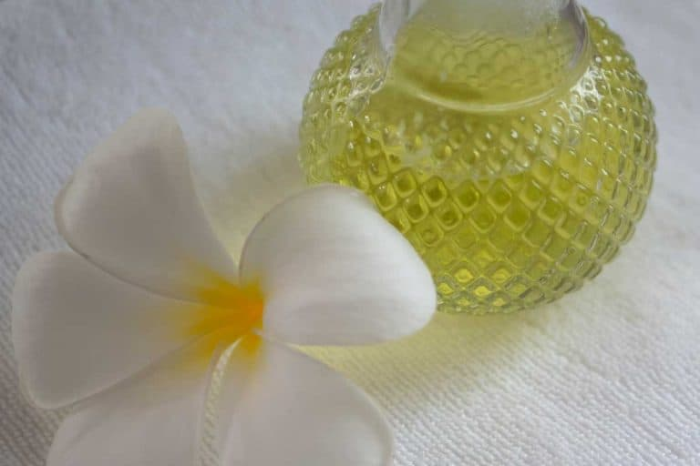 White plumeria flower and oil bottle on bed with white sheets, How To Remove Body Massage Oil From Sheets?