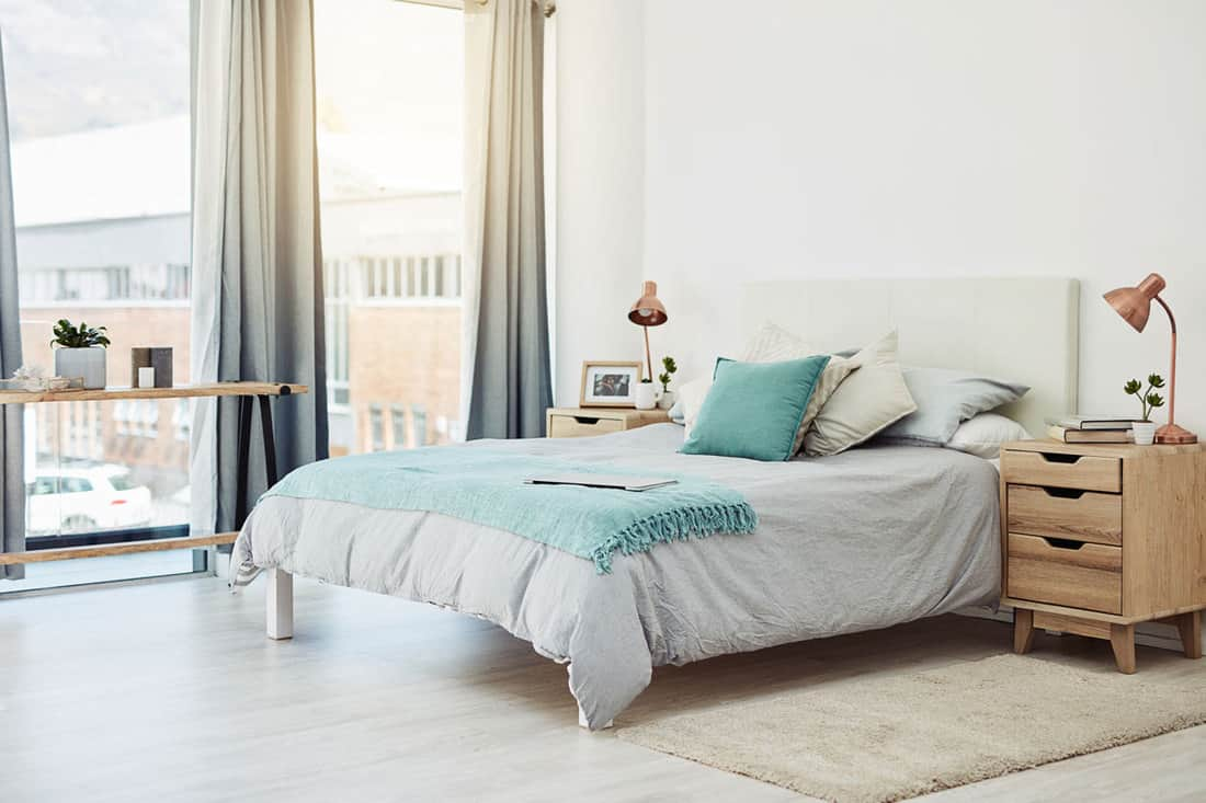 White walled bedroom with white flooring and a blue bedding set