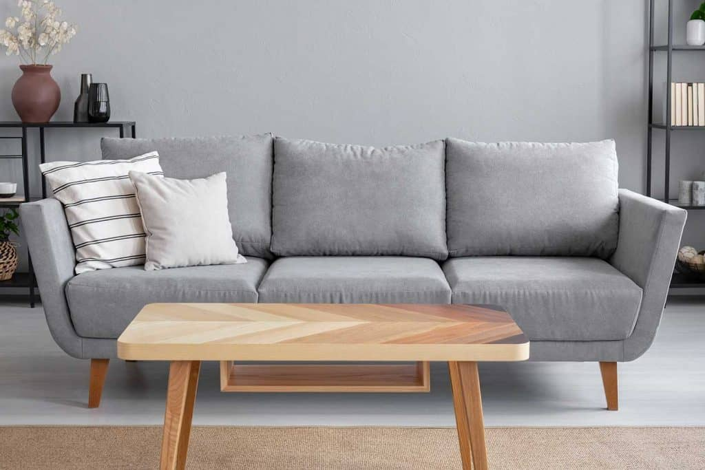 Wooden table and big grey couch with throw pillows in living room