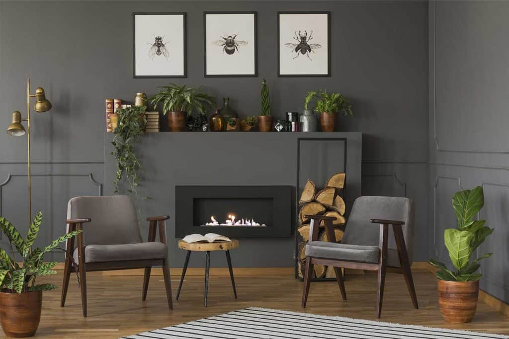 Wooden table between gray armchairs and dark gray walls in retro flat interior with fireplace under posters