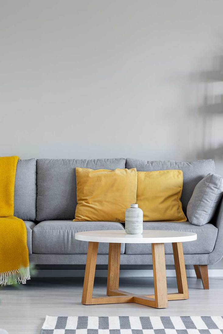 Yellow throw pillows and blanket on grey couch in living room interior with round wooden table