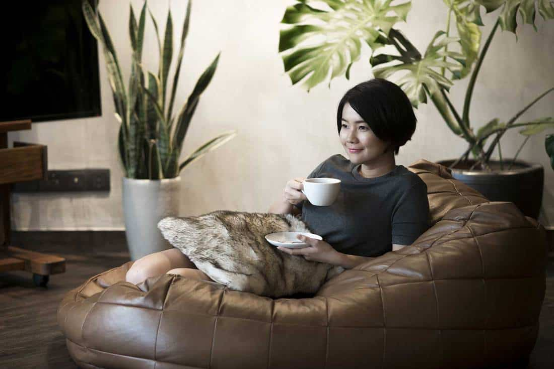 Young woman drinking coffee in a cozy living room with house plants