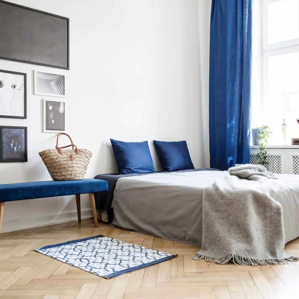 A beautiful bedroom with a blue curtain, blue table, and blue throw pillows