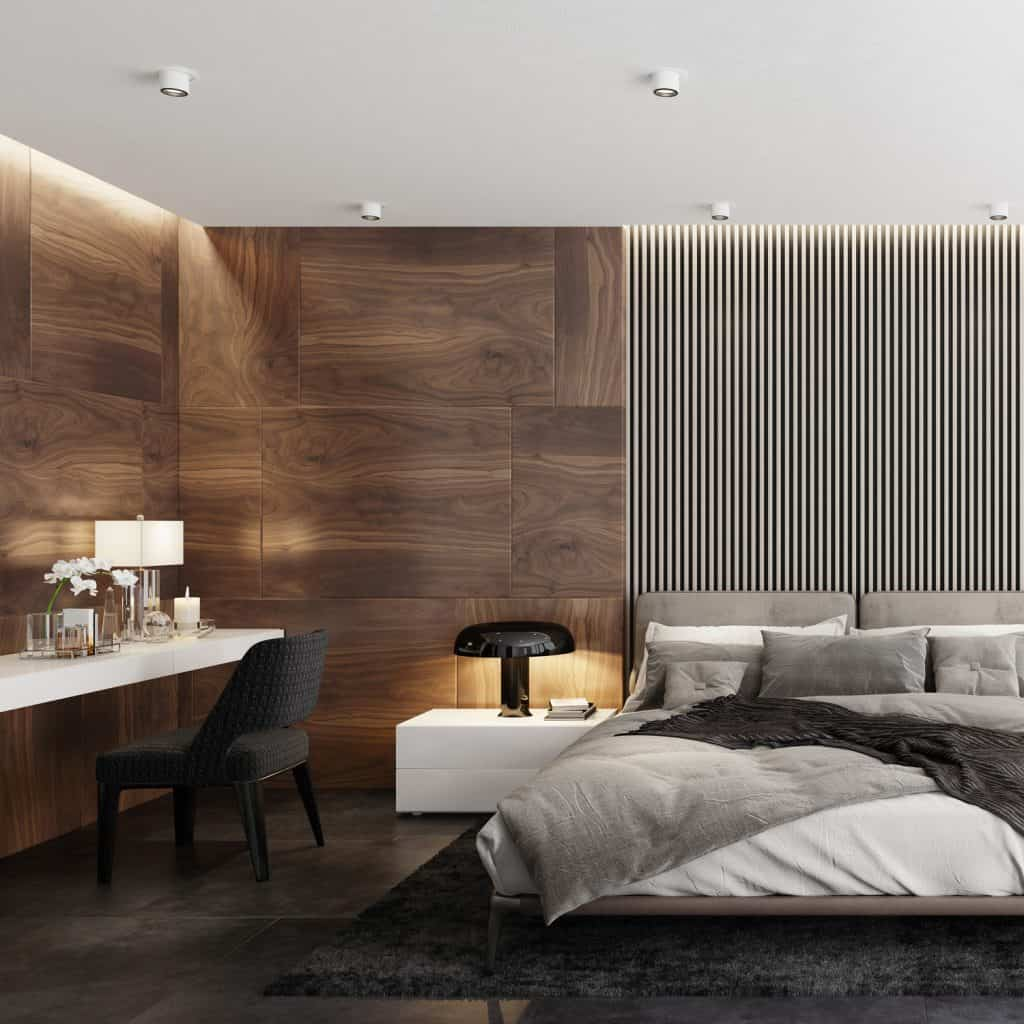 A bedroom with a trellis like decorative section on the headboard ad wood paneling on the side