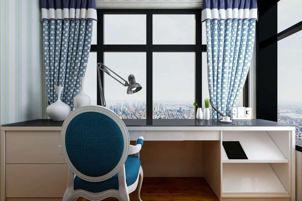 A beautiful desk with a blue chair, blue curtains, and a panoramic view of a city