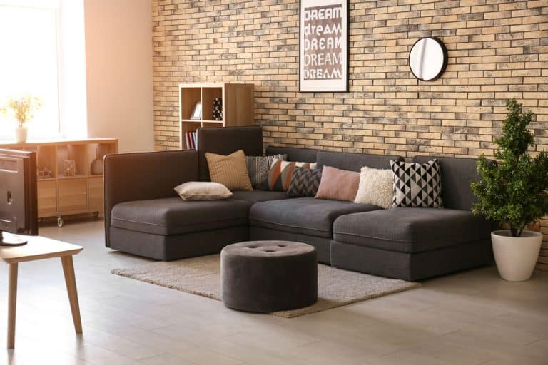 A black couch with assorted colored throw pillows and a black ottoman, What Color Ottoman Goes With A Black Couch?