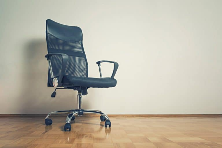 A blue office chair placed at the corner of a room , Should You Get A Cushion For Your Office Chair?