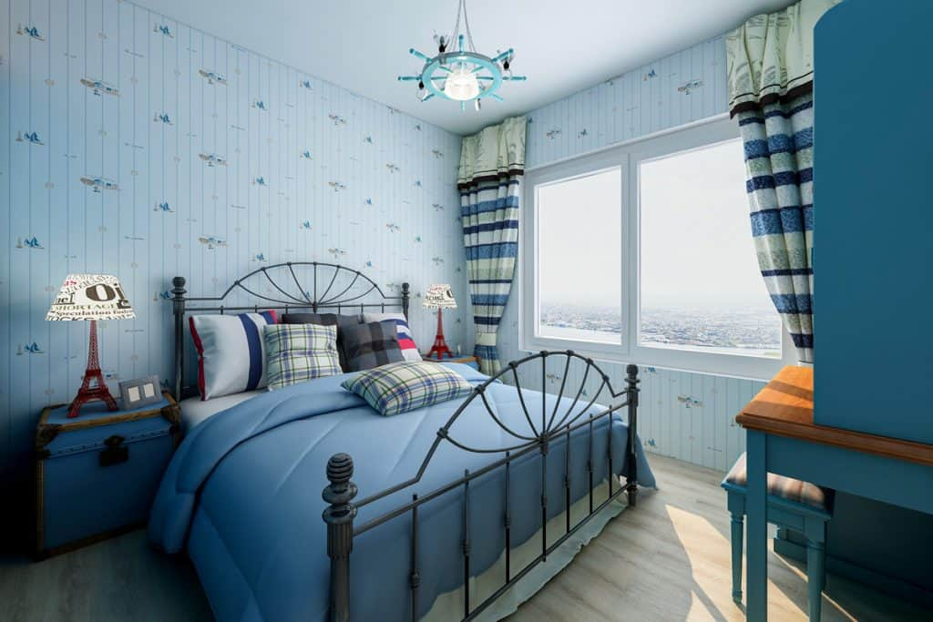 A blue themed bedroom with a blue bed and a striped blue curtain