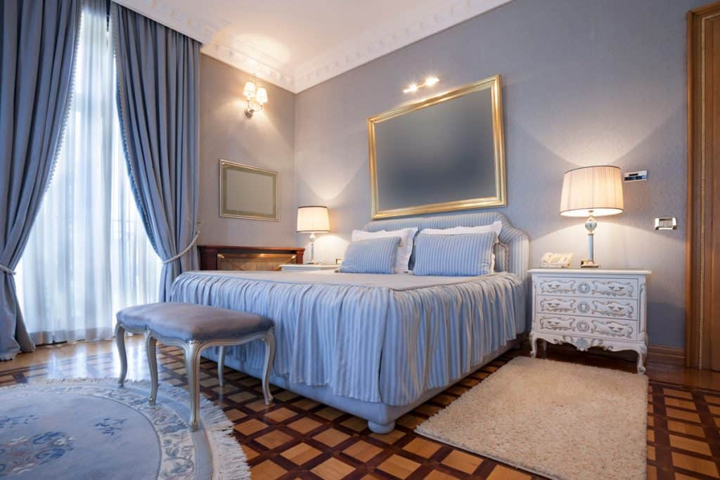 A blue themed bedroom with a blue curtain on the side