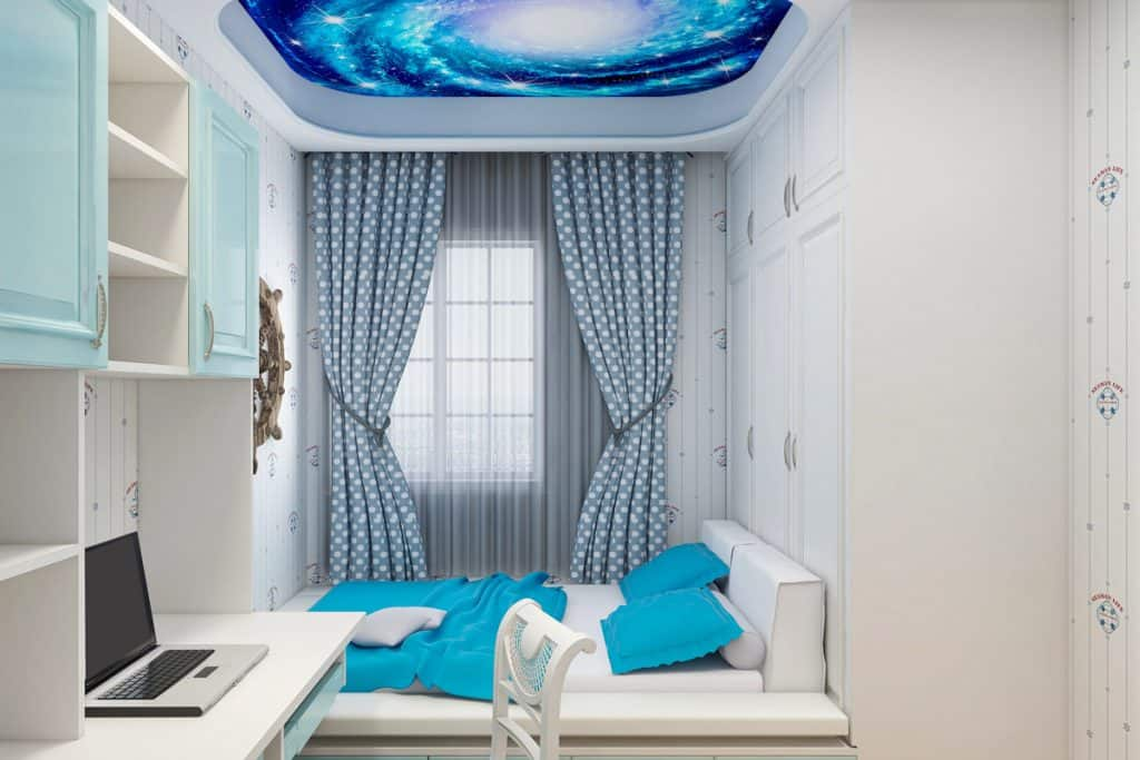 A blue themed bedroom with a galaxy wallpaper on the ceiling and a bed with blue pillows and blankets