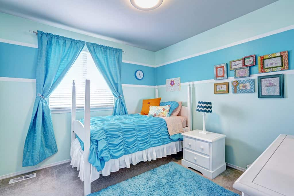 A blue themed bedroom with blue blankets and a blue curtain