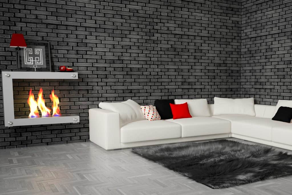 A brick decorative wall and a white corner sofa with white throw pillows