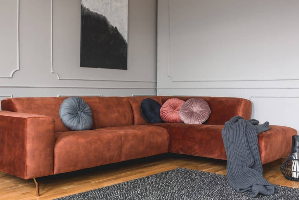 A brown sectional sofa with round throw pillows and a white colored wall
