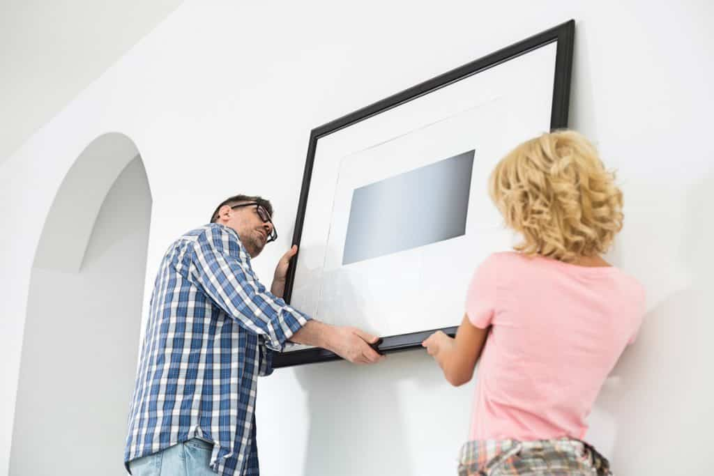 A couple placing a big picture frame on their living room wall