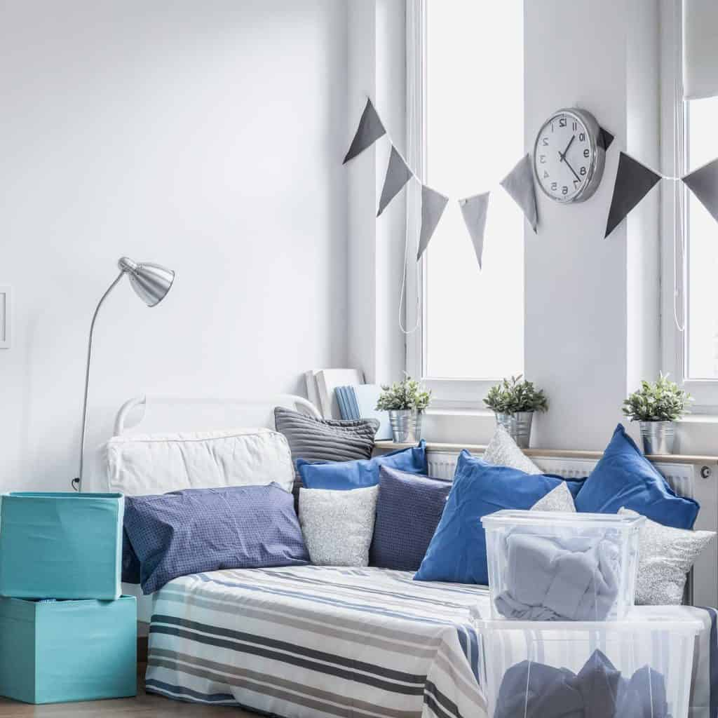 A cozy blue and gray themed bedroom with plants by the window