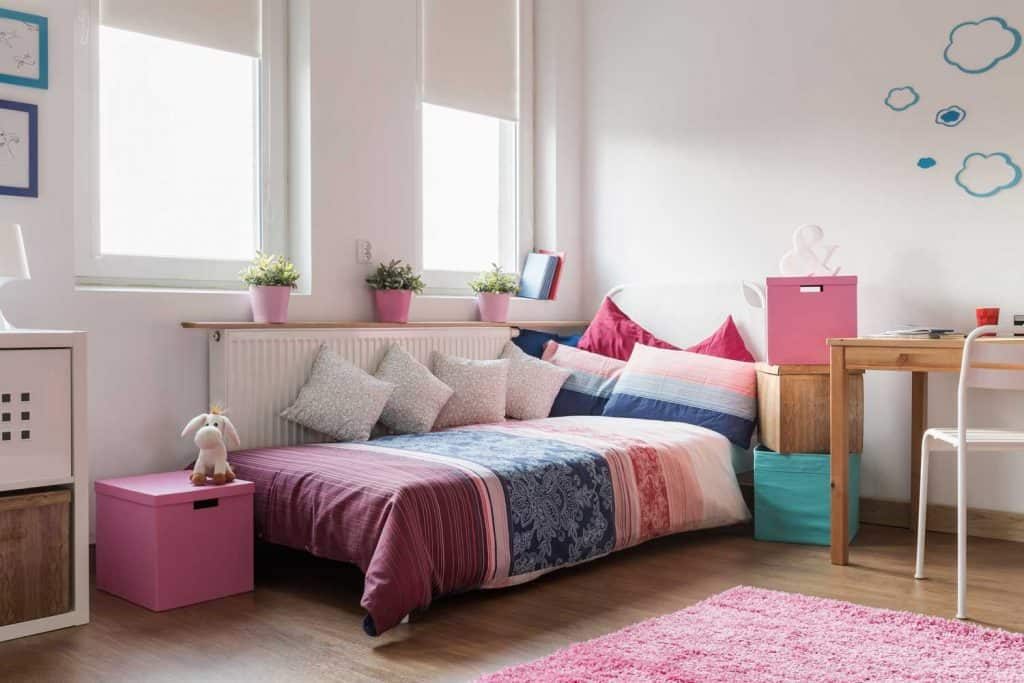 A cute pink theme bedroom designed for a little girl with bright windows and pots of plants