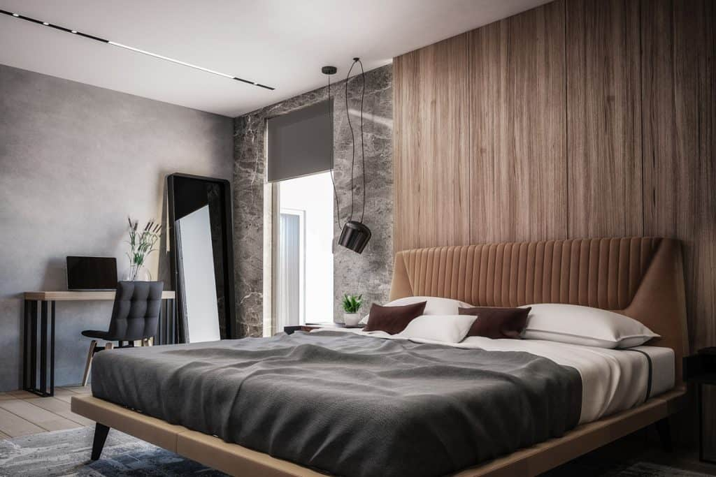 A gorgeous bedroom with a gray bed and a wooden paneled headboard
