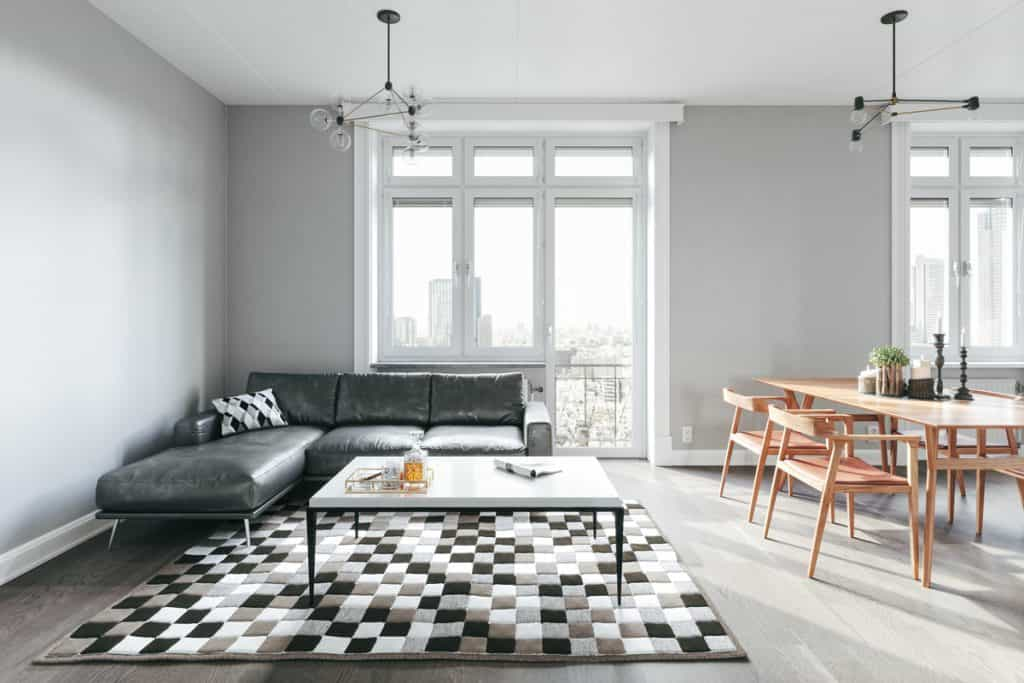 A luxurious condominium unit with a gray flooring, gray sectional sofa, and checkered rug