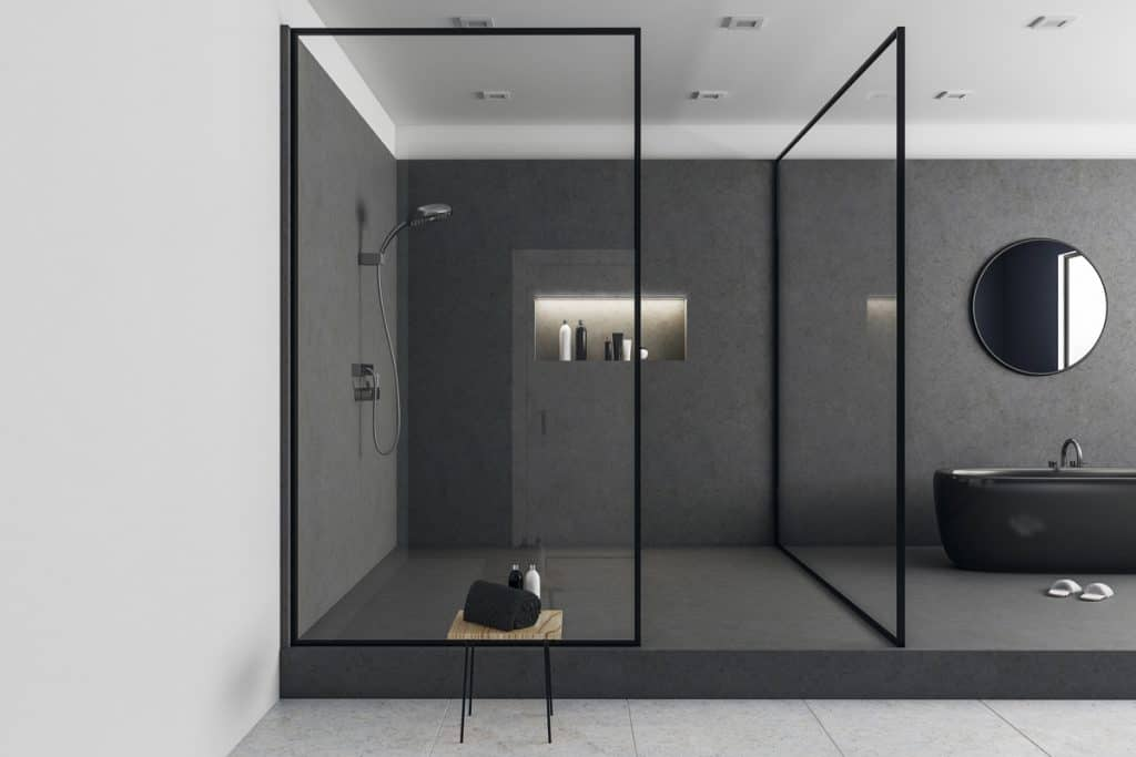 A modern bathroom with a dark gray texture on the flooring and walls