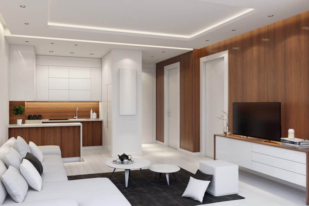 A modern condominium with wooden panels installed on the wall and an all white colored furnitures