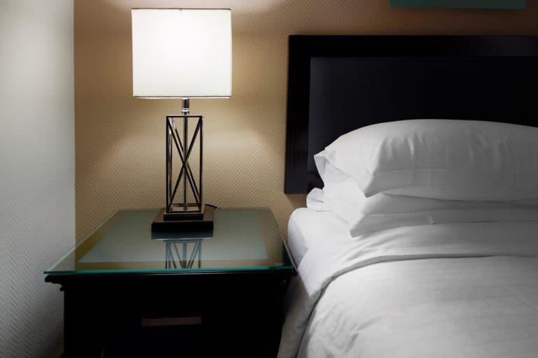 A modern designed lamp placed on a nightstand beside a bed, Do You Need Two Nightstands? [Design rules and suggestions]