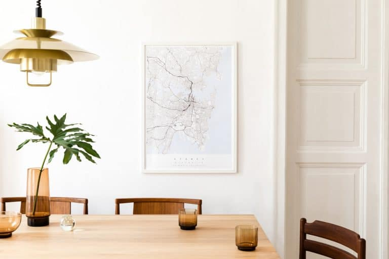 A modern dining room with a picture frame hanged on a white wall, How To Hang Heavy Frames Without Nails [3 Easy Ways]