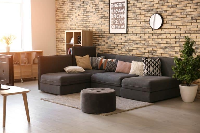 A modern living room with a dark colored sectional sofa and an ottoman up front for a foot rest, Can An Ottoman Be Used For Sitting?