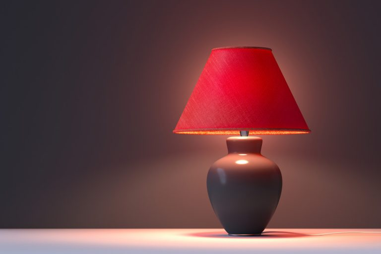 A red colored lamp shade turned on with a gray background, Can You Wash Lamp Shades in the Dishwasher?