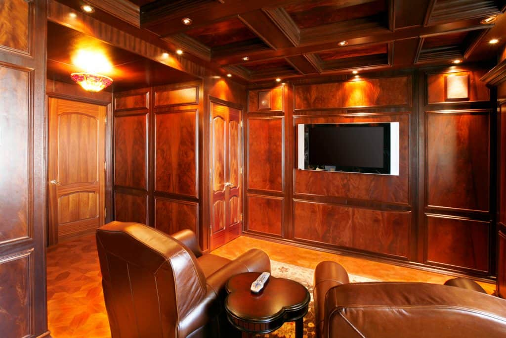 A rustic themed entertainment room with wooden paneling and a TV on the wall